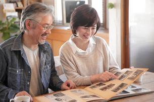 古いアルバムを見るミドル夫婦の写真素材 [FYI01469881]