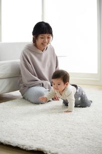 白いラグの上でハイハイをする赤ちゃんと見守る母の写真素材 [FYI01469949]