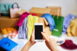箱から出る服や帽子などが散らかった部屋とスマートフォンの写真素材 [FYI01469958]