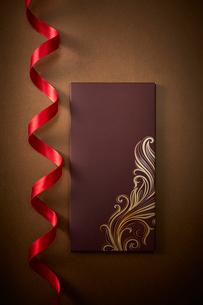 ゴールドの背景に置かれた赤いリボンと茶色い箱の写真素材 [FYI01470039]