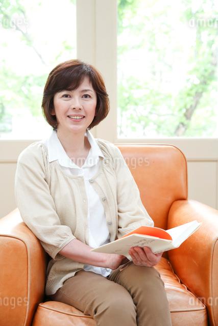 ソファで読書をするミドル女性の写真素材 [FYI01470054]