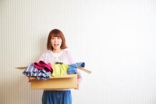 段ボール箱に入った服を運ぶ女性の写真素材 [FYI01470118]