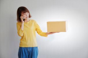 壁の前で荷物を持って電話をする女性の写真素材 [FYI01470184]