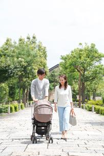 新緑の住宅街でベビーカーを押す若いカップルの写真素材 [FYI01470185]