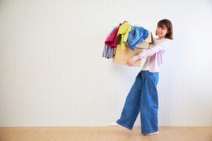 段ボール箱に入った服を運ぶ女性の写真素材 [FYI01470223]