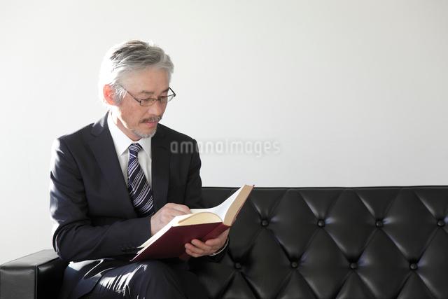 ソファで本を読むミドルビジネスマンの写真素材 [FYI01470278]
