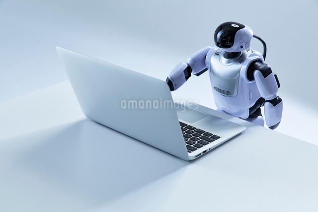 ノートパソコンを操作するミニロボットの写真素材 [FYI01470380]