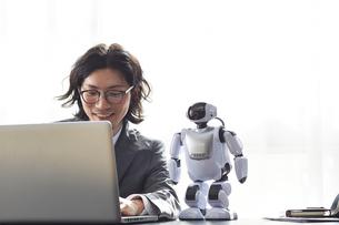 ロボットとパソコンを見るスーツを着た男性の写真素材 [FYI01470381]