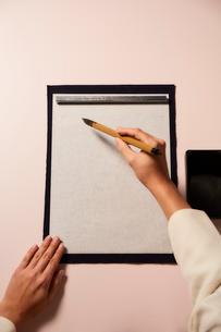 薄いピンクの背景の書道をする女性の手の写真素材 [FYI01470512]