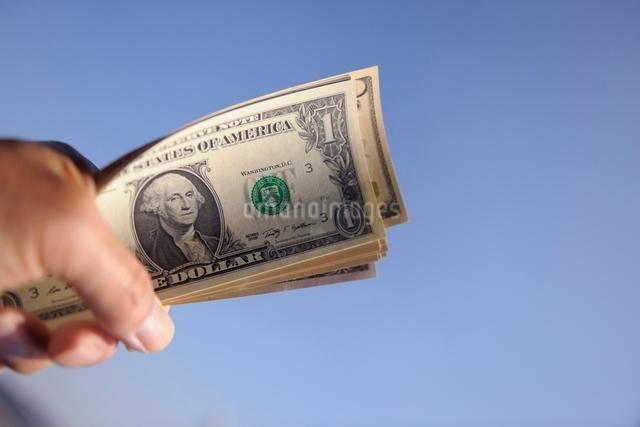 青空のドル紙幣を握る手の写真素材 [FYI01471070]