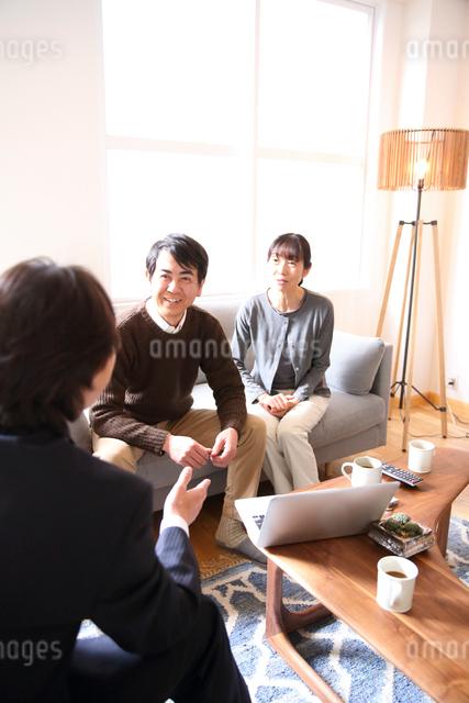 ビジネスマンから説明を受けるミドルカップルの写真素材 [FYI01471164]