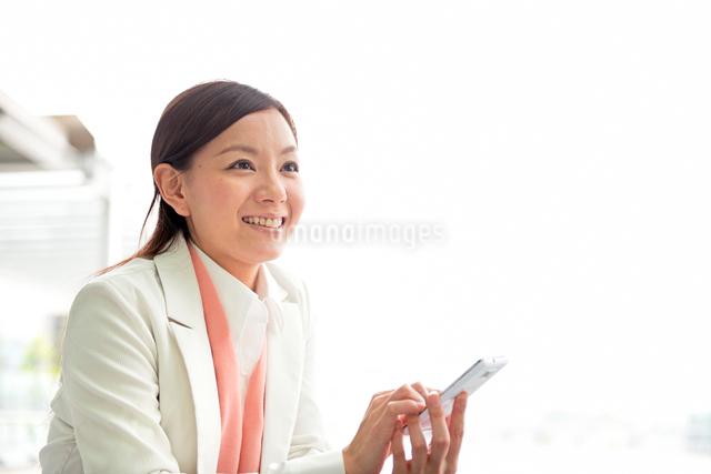 オフィスビルの前でスマートフォンと女性の写真素材 [FYI01471258]