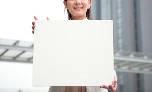 オフィスビルの前で白色ボードと女性の写真素材 [FYI01471261]