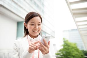 オフィスビルの前でスマートフォンと女性の写真素材 [FYI01471311]