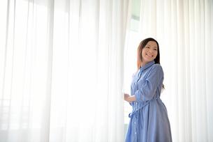 明るい窓際の若い女性の写真素材 [FYI01471403]