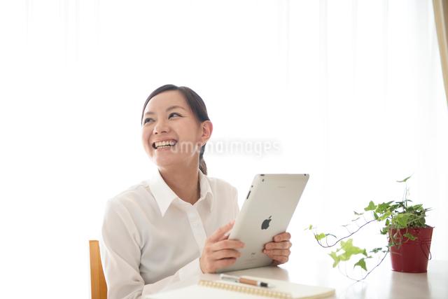 オフィス内でタブレットPCと女性の写真素材 [FYI01471432]