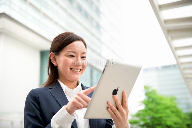 オフィスビルの前でタブレットPCと女性の写真素材 [FYI01471470]