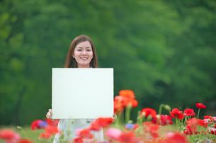 お花畑で笑顔の女性とホワイトボードの写真素材 [FYI01471492]