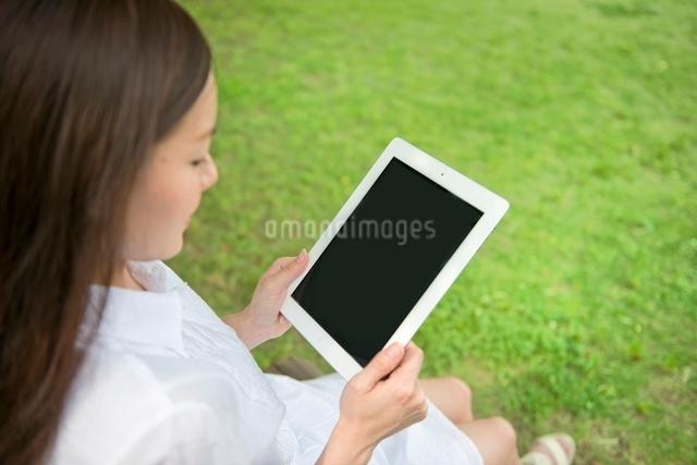 昼休みのオフィス街でタブレットPCと女性の写真素材 [FYI01471641]