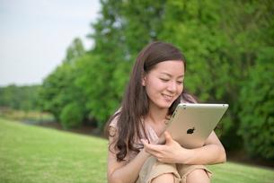 新緑の丘の上で笑顔の女性とタブレットPCの写真素材 [FYI01471834]
