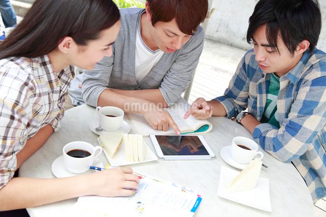 カフェで学ぶ3人の男女大学生の写真素材 [FYI01472198]