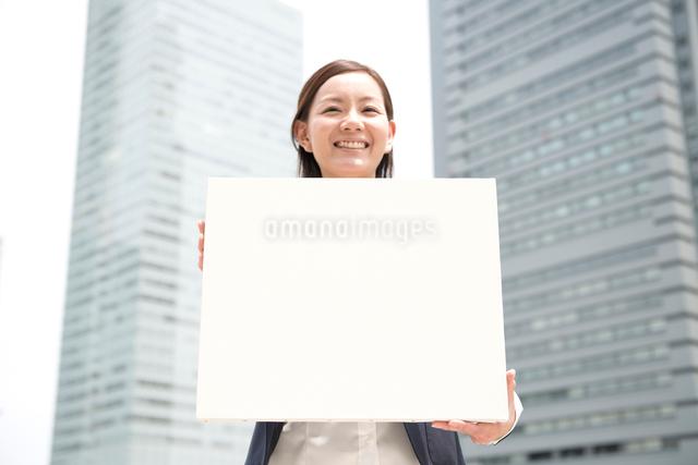 オフィスビルの前で白色ボードと女性の写真素材 [FYI01472255]