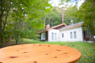 緑の中の白い家と木目テーブルの写真素材 [FYI01472260]