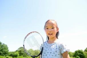 緑の草原とテニスラケットを持つ笑顔の女の子の写真素材 [FYI01472274]
