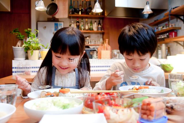 夕食を楽しむ幼い兄妹の写真素材 [FYI01472404]