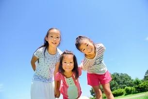 青空と緑の草原と笑顔でのぞく女の子達の写真素材 [FYI01472472]