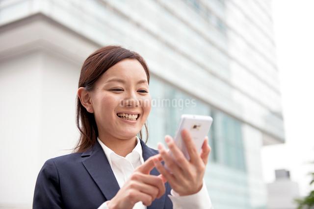 オフィスビルの前でスマートフォンと女性の写真素材 [FYI01472618]