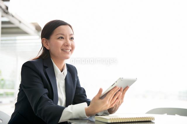 オフィスビルの前でタブレットPCと女性の写真素材 [FYI01472699]