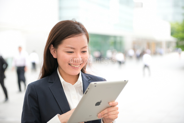 オフィスビルの前でタブレットPCと女性の写真素材 [FYI01473019]
