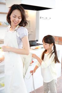 母親のエプロンの紐を締める女の子の写真素材 [FYI01473950]