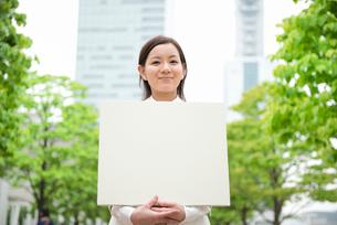 新緑のオフィスビルの前で白ボードと女性の写真素材 [FYI01474903]