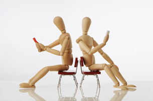 いすに座り携帯電話を使う2人のモデル人形の写真素材 [FYI01475293]