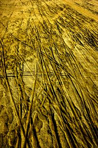 砂のグラウンドに自転車の轍と足跡の写真素材 [FYI01475755]