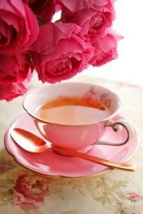 赤バラとピンク色のティーカップに入った紅茶の写真素材 [FYI01476776]