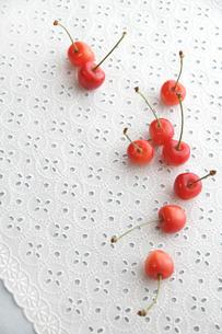 白いレースの上の赤いさくらんぼの写真素材 [FYI01476793]
