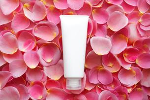 一面のバラの花びらの上の白い化粧品のチューブの写真素材 [FYI01476833]