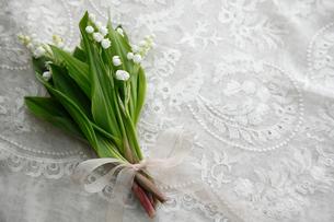 刺繍のある白い布の上に置かれた小さなスズランの花束の写真素材 [FYI01476835]