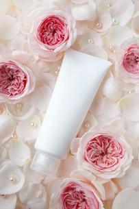 敷き詰められたバラの花と花びらの上の化粧品のチューブの写真素材 [FYI01476999]