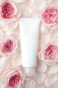 敷き詰められたバラの花びらの上の化粧品のチューブの写真素材 [FYI01477185]