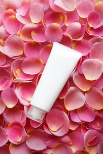 一面のバラの花びらの上の白い化粧品のチューブの写真素材 [FYI01477239]