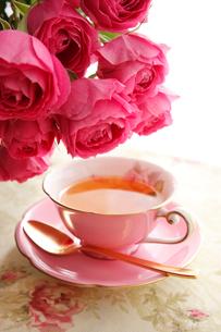 赤バラとピンク色のティーカップに入った紅茶の写真素材 [FYI01477282]