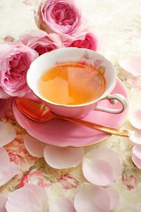 紅茶の入ったティーカップとピンクのバラの花の写真素材 [FYI01477398]