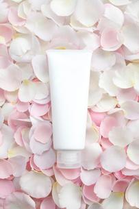 一面のバラの花びらの上の白い化粧品のチューブの写真素材 [FYI01477948]