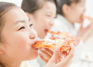 ピザを食べる小学生の女の子の写真素材 [FYI01478934]