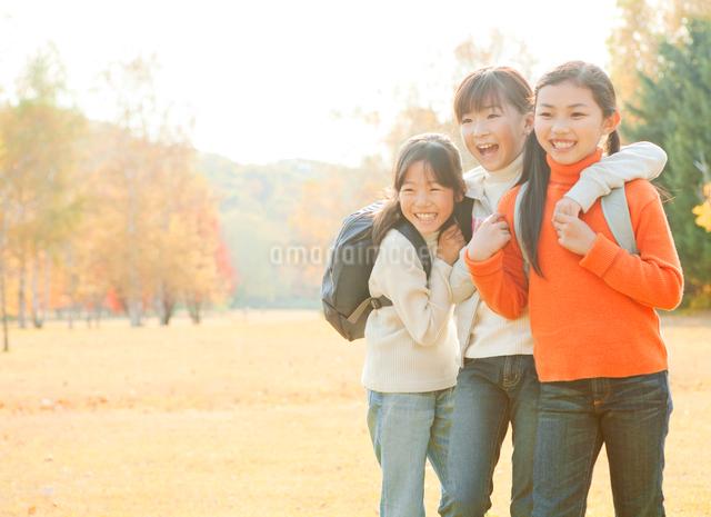 紅葉の中で遠足を楽しむ小学生の女の子3人の写真素材 [FYI01478947]