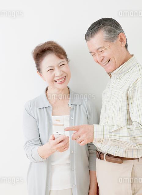 携帯電話を操作する60代の夫婦の写真素材 [FYI01478954]